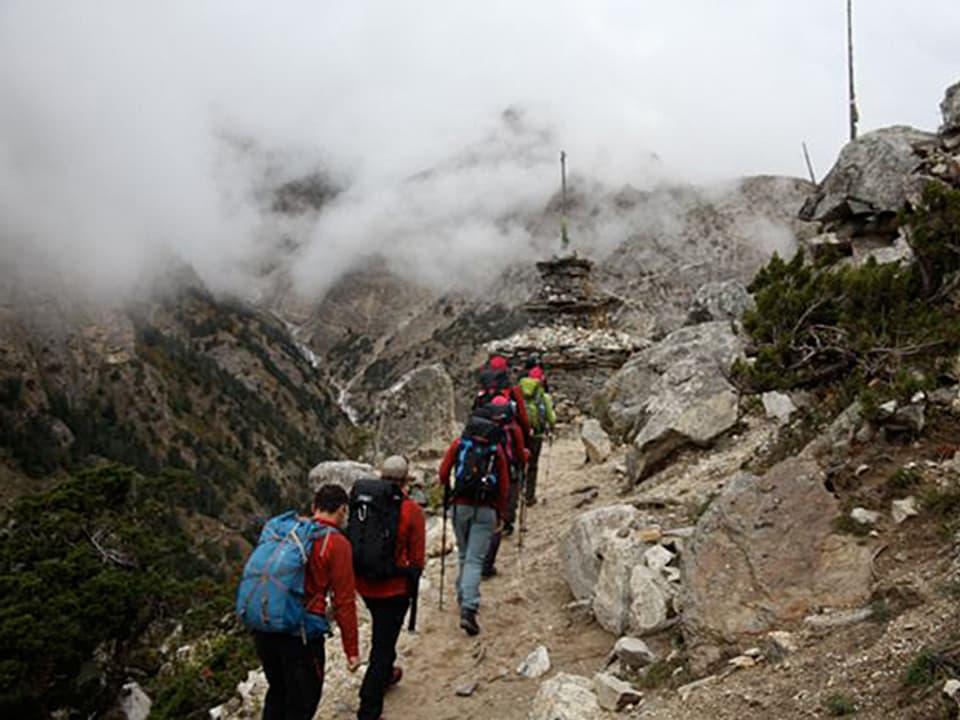 Expeditionsteilnehmer auf einem schmalen Pfad und Nebel beim Aufstieg zum Basislager.