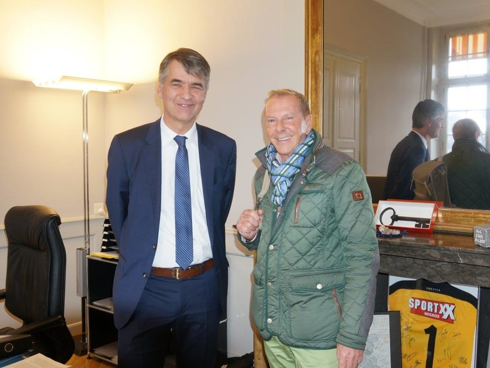 Im Büro des Stadtpräsidenten unterhalten sich Alec von Graffenried links, Kurt Aeschbacher rechts. Im Hintergrund spiegelt sich die Szene.