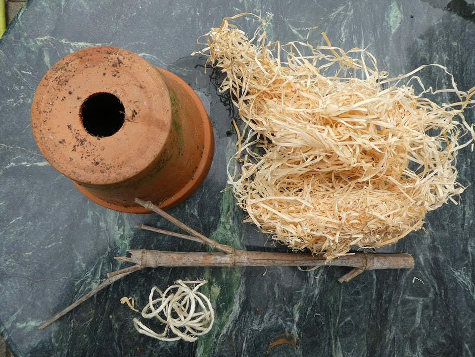 Ein Tontopf, Holzwolle, Schnur und ein Stück eines Asts.