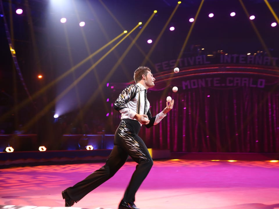 Michael Ferreri jongliert mit sieben Bällen gleichzeitig, während er den achten auf dem Kopf balanciert.