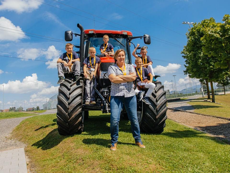Lang Christina posiert vor einem Traktor mit ihren Jungschwingern.