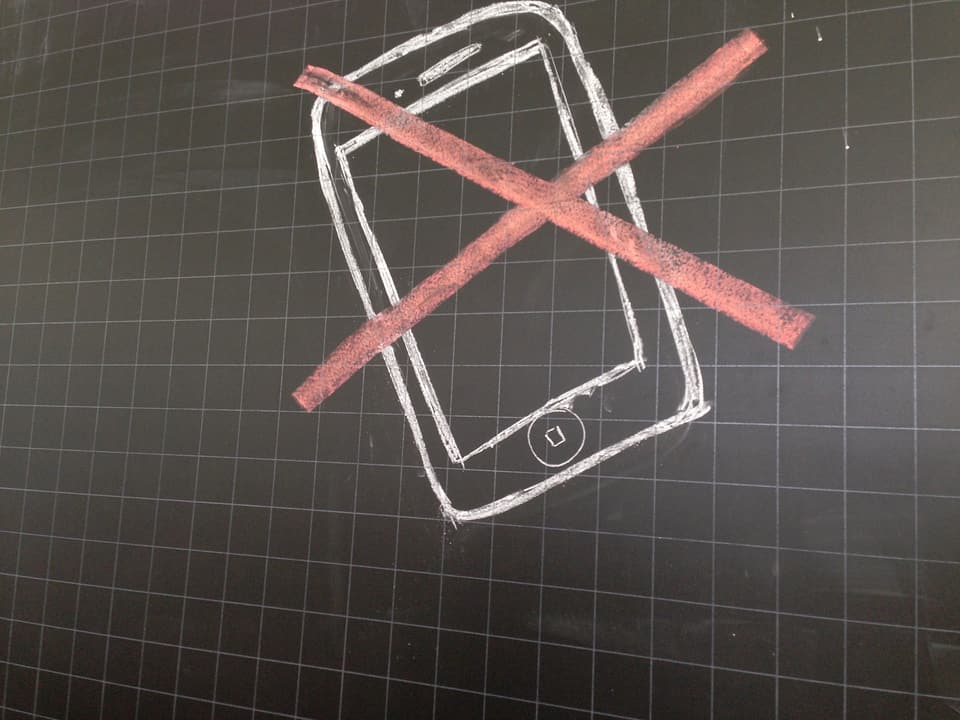 Handy-Verbot-Symbol auf Wandtafel.