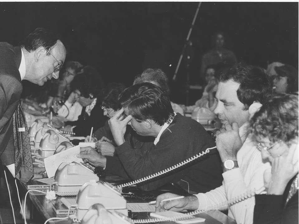 Ein Tisch mit vielen Telefonisten dran.
