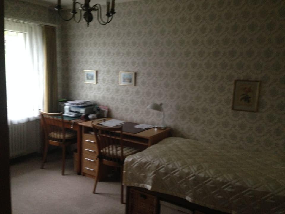 Altmodisches Zimmer mit Bett und Schreibtisch.