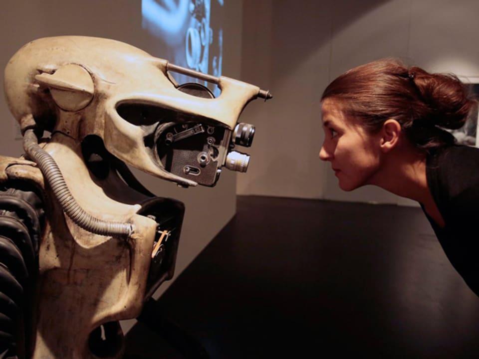 Ausstellungsbesucherin vor Alien-Figur