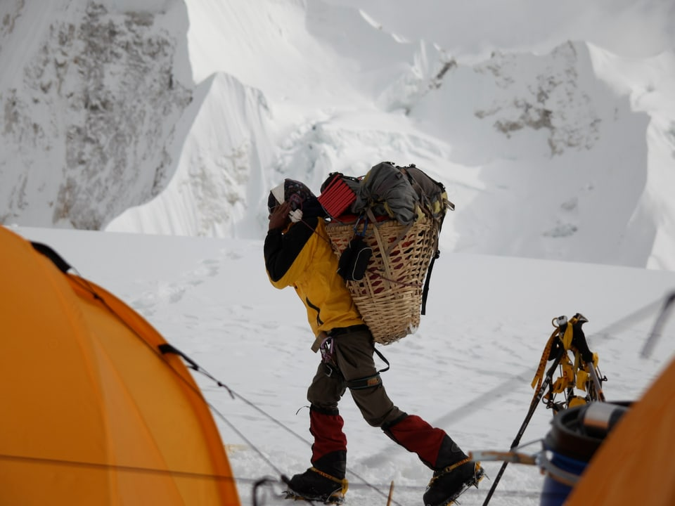 Ein Sherpa mit einem vollbepackten und geflochtenen Korb auf dem Rücken zwischen zwei Zelten.