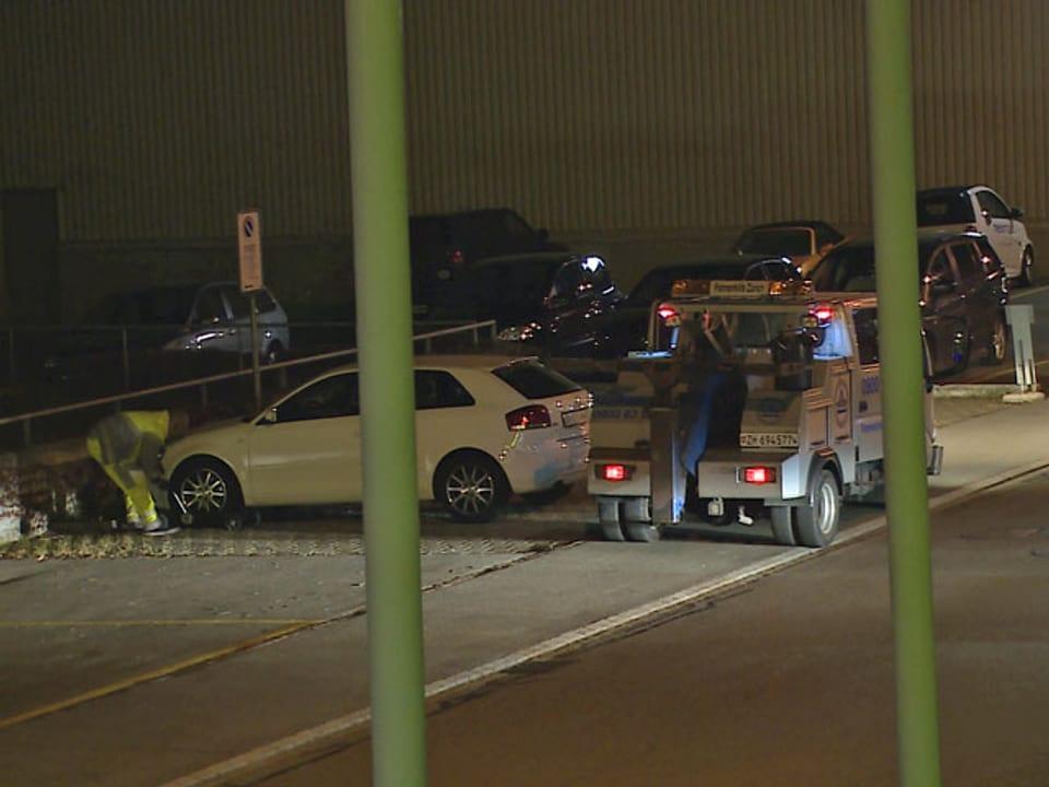Abschleppwagen beginnt seine Arbeit bei einem weissen Audi.
