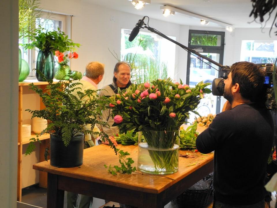 Im Blumenladen Luluderia befragt Kurt Aeschbacher einen Kunden. Dabei wird er von Kameramann Ueli Haberstich gefilmt. Der Ton wird von Max Büchel mit der Perche (Handstange) aufgenommen.