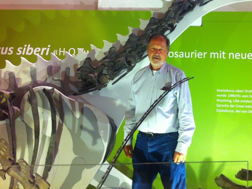 Hans-Jakob Siber posiert neben Saurier-Knochen