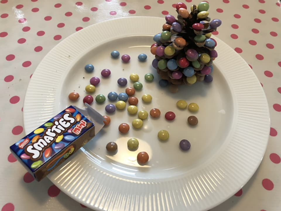 Das Bild zeigt einen mit Smarties dekorierten Tannenzapfen.