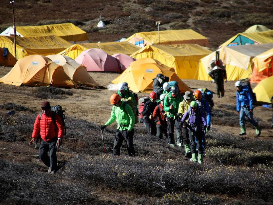 Alpinisten mit Basiscamp im Hintergrund.