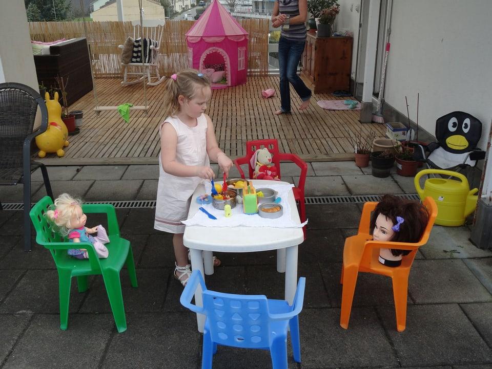 Balkon mit Kind an einem Kindertisch.