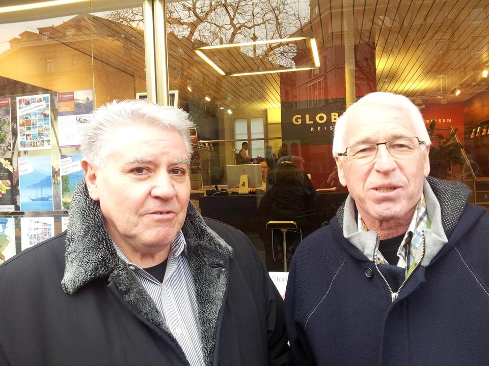 Zwei Senioren vor den grossen Fenstern eines noblen Cafés.
