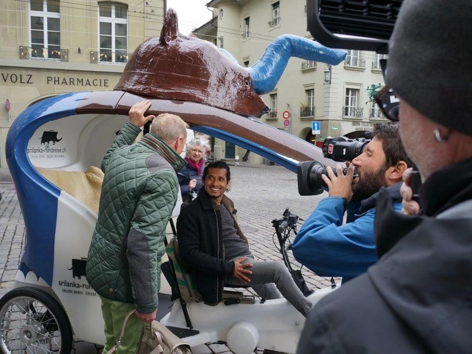 Kurt Aeschbacher stützt sich an der blauweissen Rikscha ab und unterhält sich mit Upul Vidanagama, der bereits am Steuer seiner Rikscha sitzt. Kameramann Ueli Haberstich filmt die Szene.