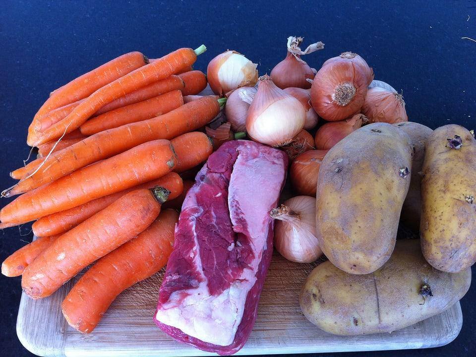 Gemüse und Fleisch auf Schneidebrett.