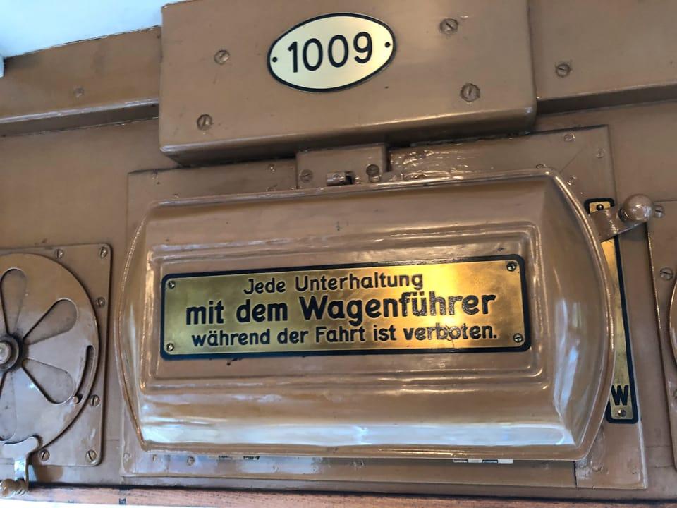 Tafel mit Auschrift «Jede Unterhaltung mit dem Wagenführer während der Fahrt ist verboten.»