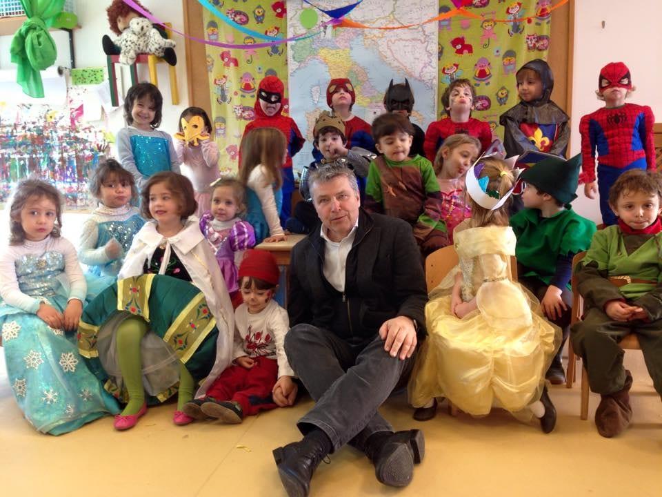 Mann sitzt vor einer Vorschul-Klasse. Die Kinder sind für den Karneval verkleidet.