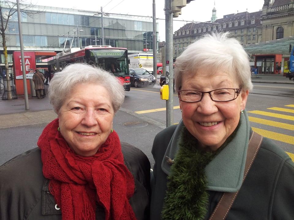 Eine Seniorin mit roten, die andere mit grünem Schal stehen beim Bahnhof Bern.