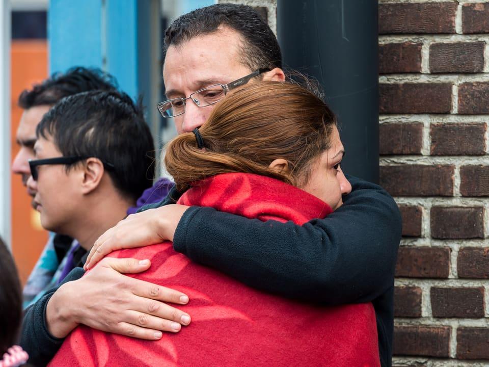 Ein Mann umarmt eine Frau in einer Wolldecke.