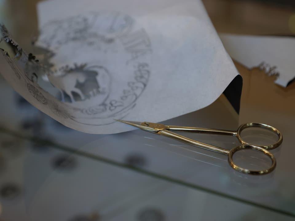 Eine goldfarbene feine Schere vor einem Blatt Papier, auf dem die Vorlage für den Scherenschnitt aufgezeichnet ist.