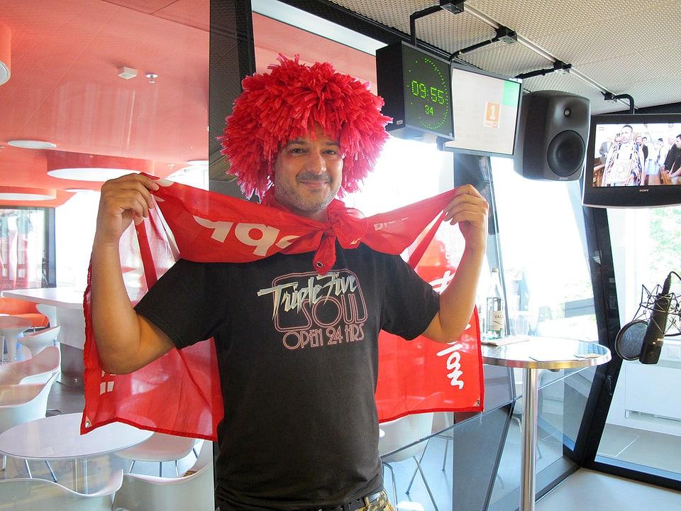 Stefan Lienhard mit Perücke und Schweizerfahne im Radiostudio.