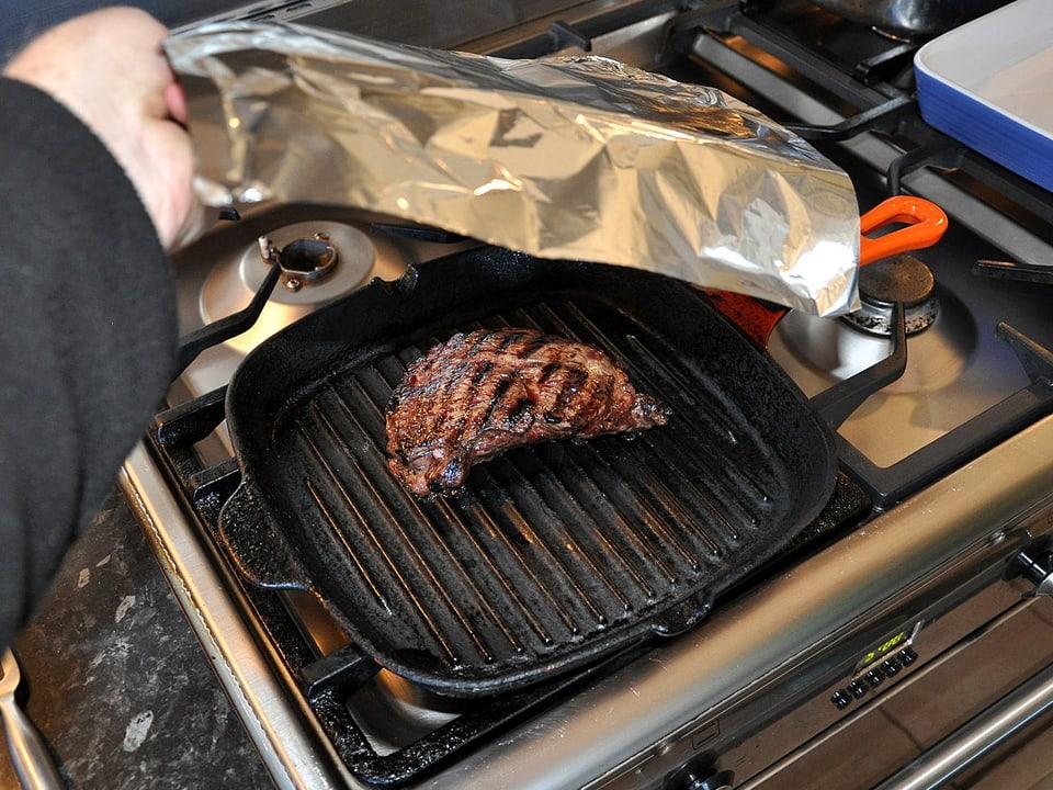 Fleisch wird mit Alufolie abgedeckt.