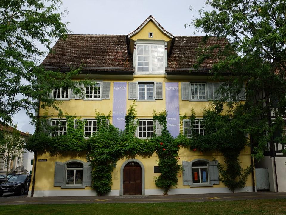 Ein dreistöckiges Haus mit hellgelber Fassade, die teils mit Efeu überwachsen ist.