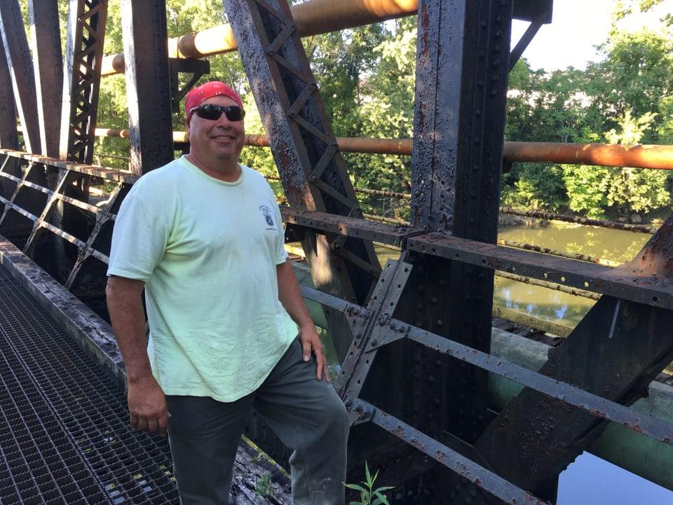 Sevi steht auf einer Brücke, ein Kopftuch um die Stirne gebunden und trägt eine schwarze Sonnenbrille. Er ist leicht beleibt.