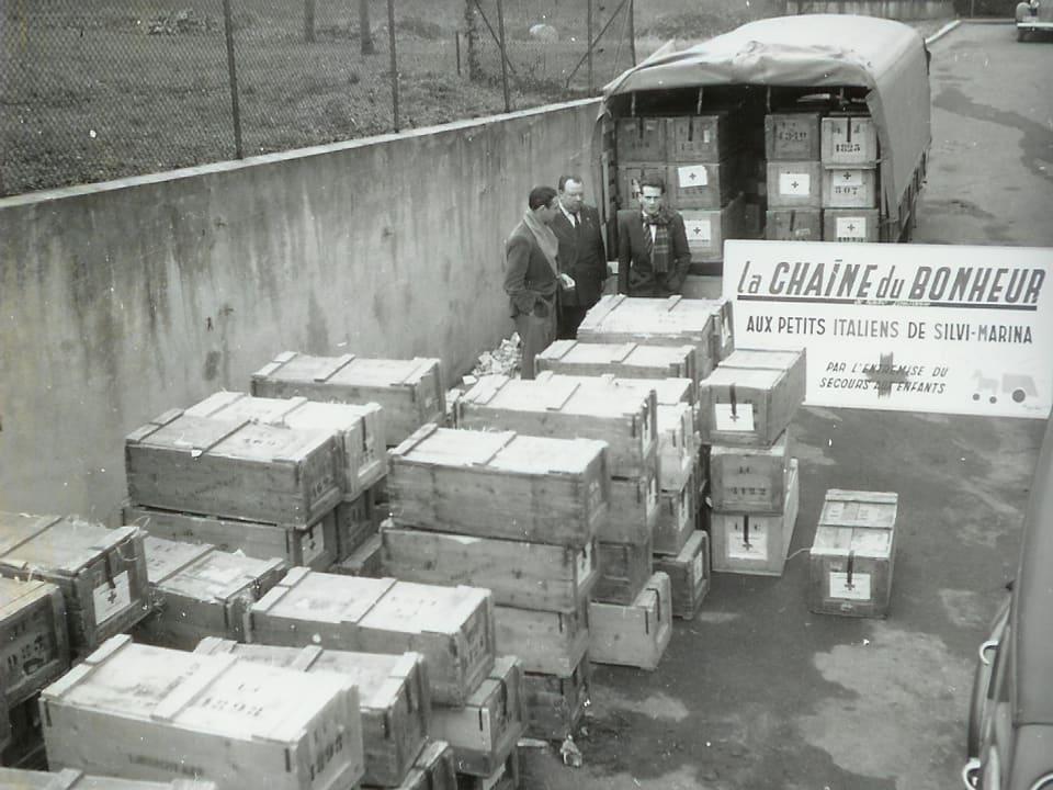 Grosse Holzkisten warten auf den Abtransport. Weit vorne ein mit Hilfsgütern beladener Lastwagen.