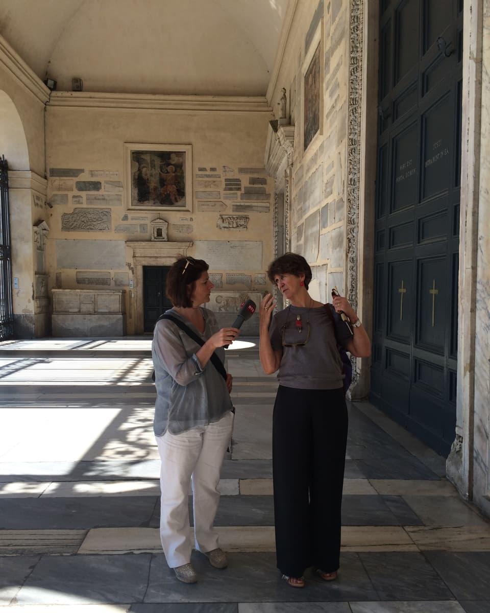 Pia Candinas ed Esther Berther avant la basilica Sta Maria in Trastevere – ina da las pli veglias basilicas da Roma.