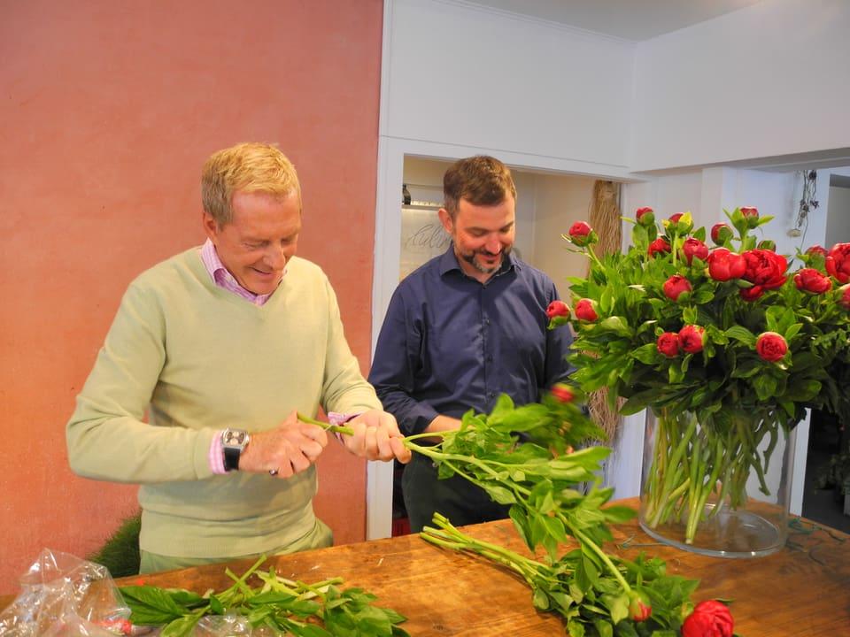 Kurt Aeschbacher (links) und Frank Wössner (rechts) schneiden mit einem Messer Pfingstrosen an. Ein grosses Glasgefäss ist bereits mit Dutzenden roter Pfingstosen gefüllt.