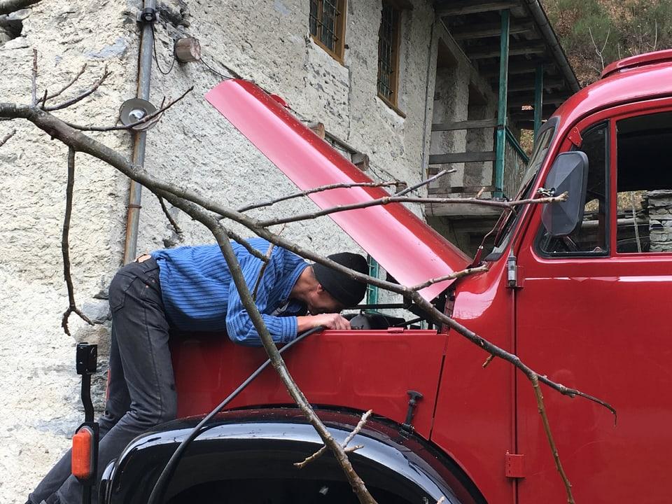 May Wälti beugt sich über den Motor seines alten Saurer-Lastwagens.