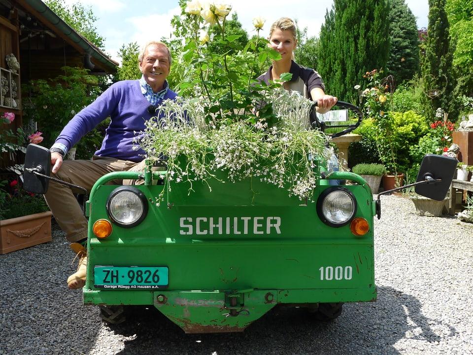 Kurt Aeschbacher und Barbara Müller am Steuer des grünen Oldtimertraktors «Schilter» mit der Autonummer ZH 9826 auf dem Kiesvorplatz des Anwesens. Auf der vorderen Ladeseite sind weisse Polsterpflanzen und ein gelber Rosenbusch zu erkennen.