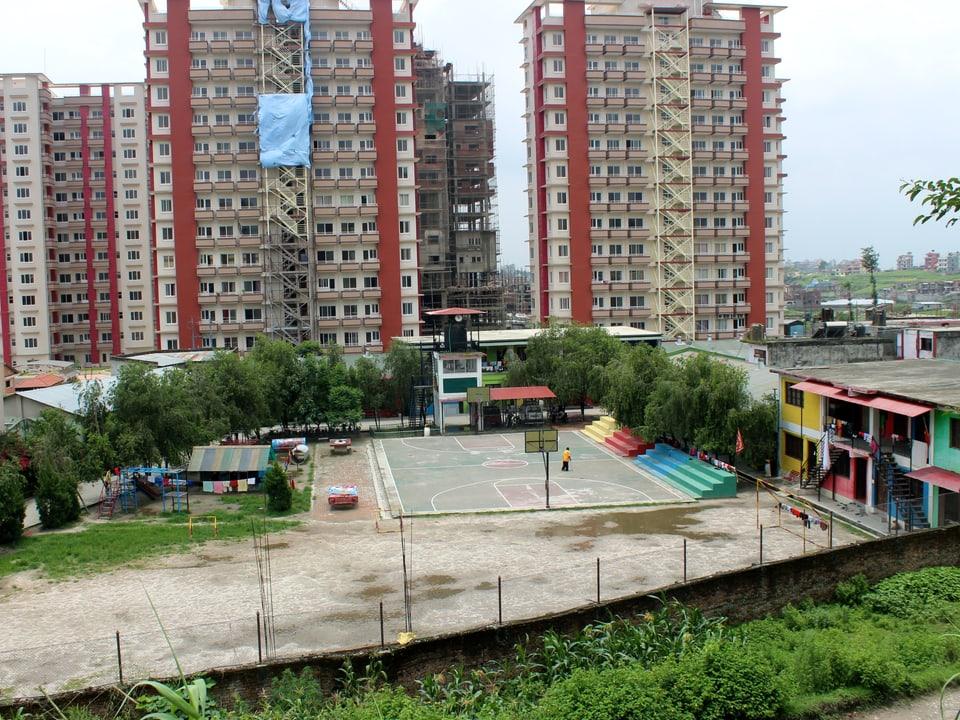 Hochhäuser in Kathmandu im Hintergrund und im Vordergrund der Spielplatz und die Anlage des Heims.