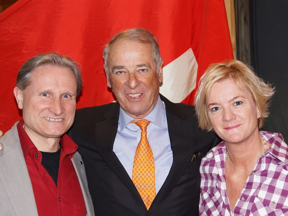 Die drei stehen vor Schweizerflagge.
