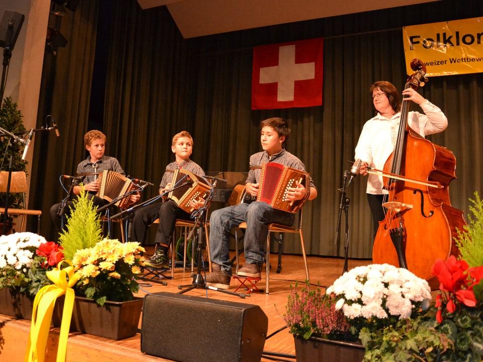 Drei junge Schwyzerörgelispieler werden von einer Musikantin auf dem Kontrabass begleitet.
