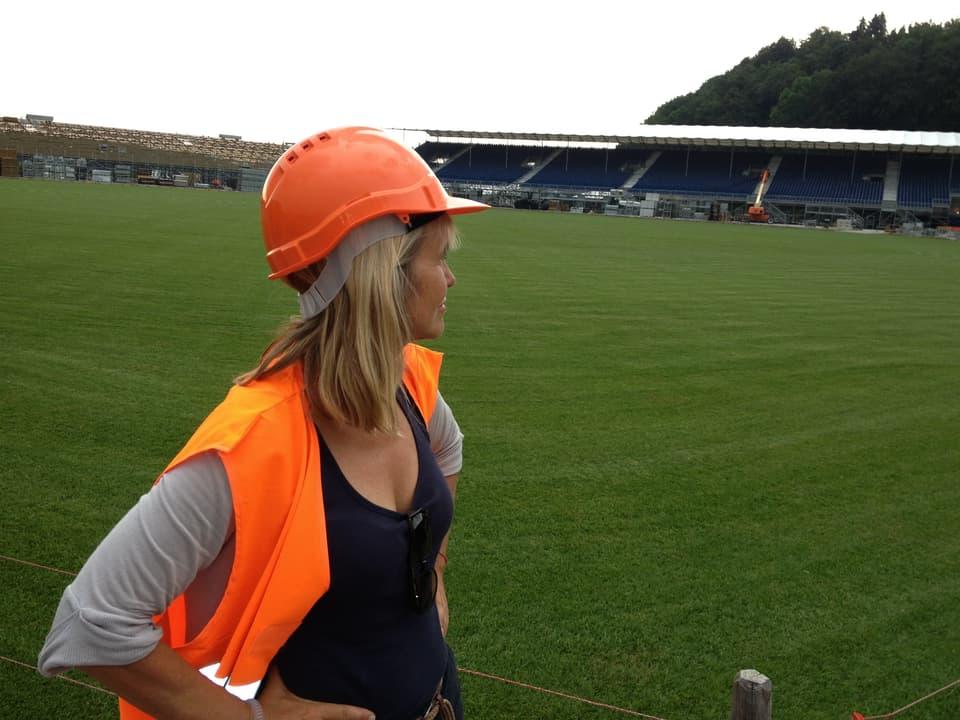 Redaktorin Christine Hubacher mit oranger Warnweste und Helm bei der Festplatzbesichtigung.