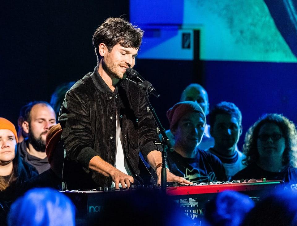 Ein junger Mann spielt auf einem Keyboard und singt.