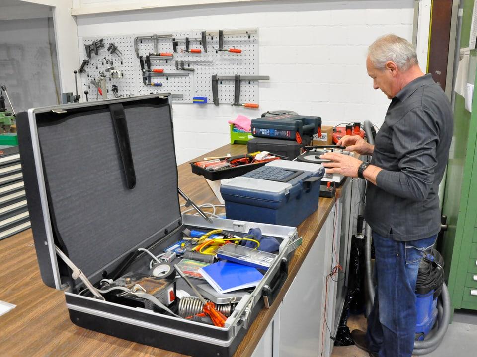 Ein Mann überprüft einen Plattenspieler. Neben ihm liegt ein Kopper mit Werkzeug.