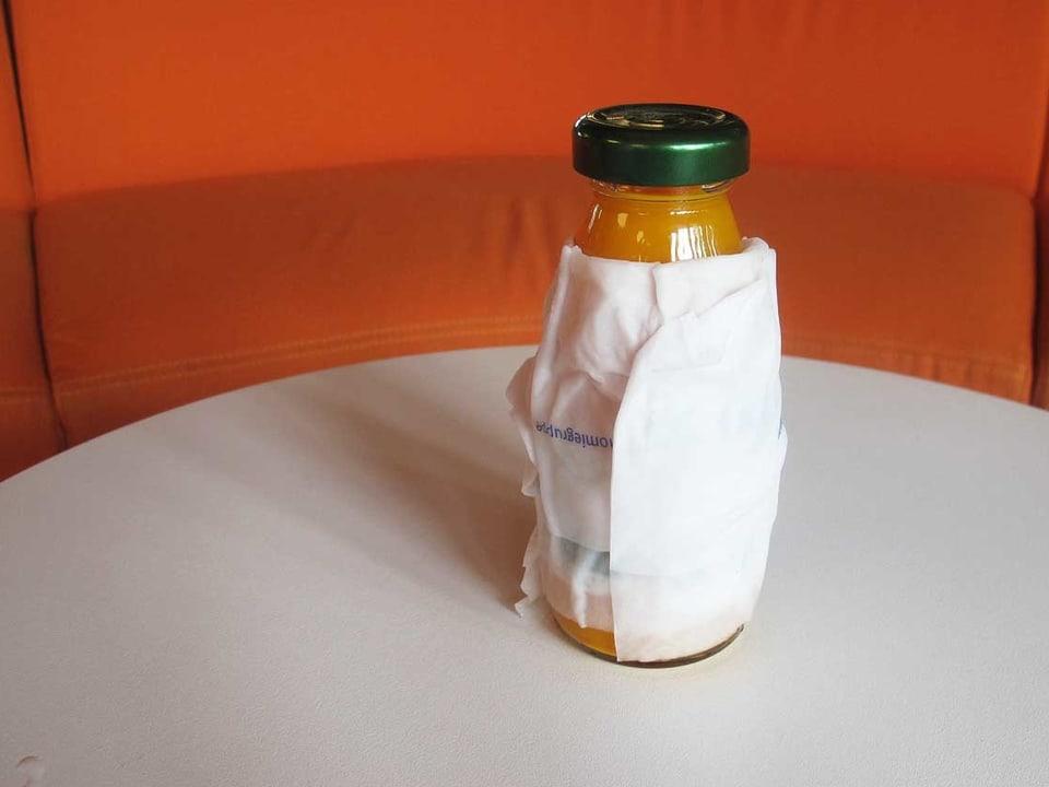 Eingewickelte Getränkeflasche auf einem Tisch.