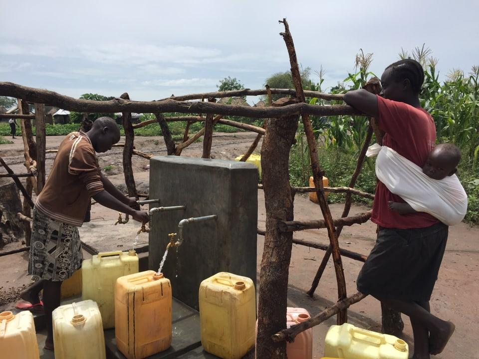 Menschen lassen an einem Brunnen Wasser in Kanister.