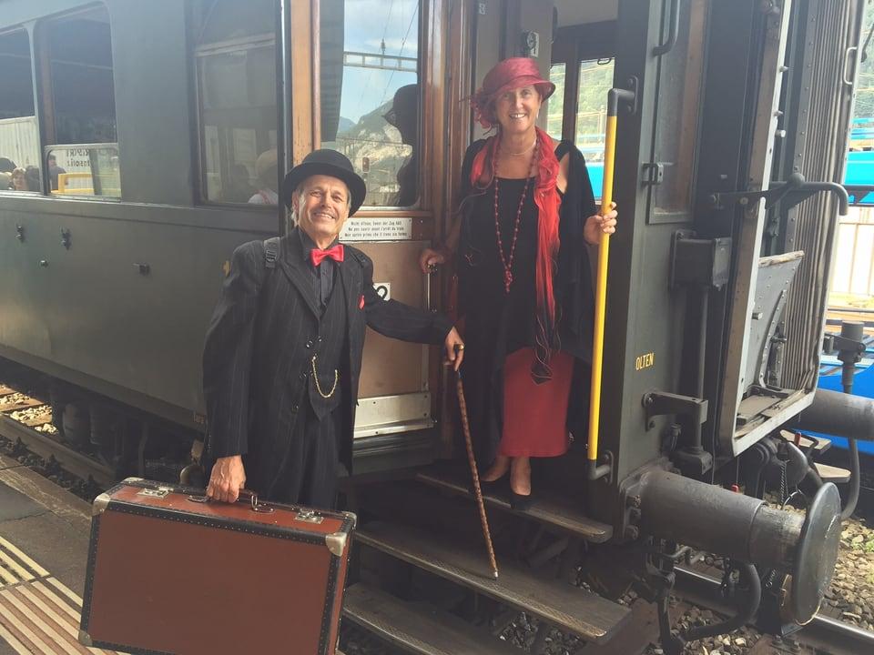 Mann und Frau in historischer Kleidung steigen in den Zug ein