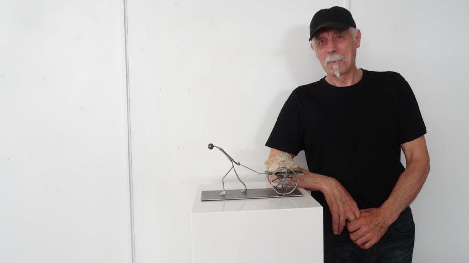 L'artist Fis Guldimann cun sia figura da fier e crap.
