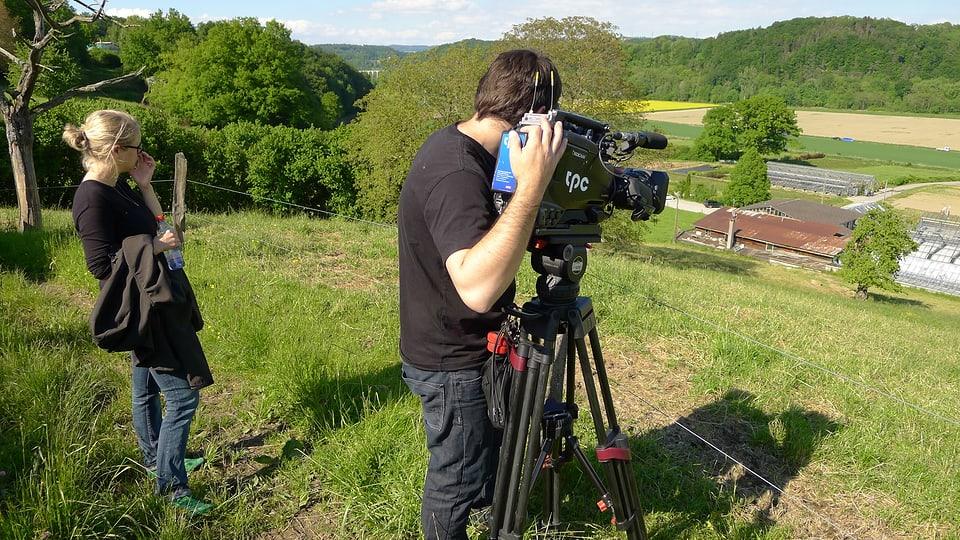 Redaktorin Pia Liechti schaut Kameramann Ueli Haberstich über die Schulter, der die Gärtnerei Linder von der Weide aus filmt.