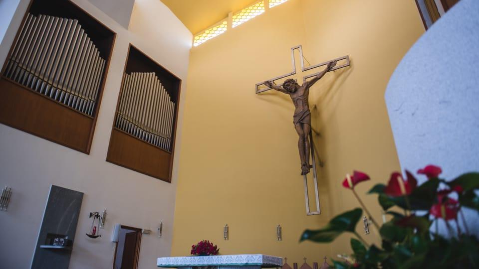 Il crucifix e l'orgla integrada en la parait da la baselgia moderan San Fedele