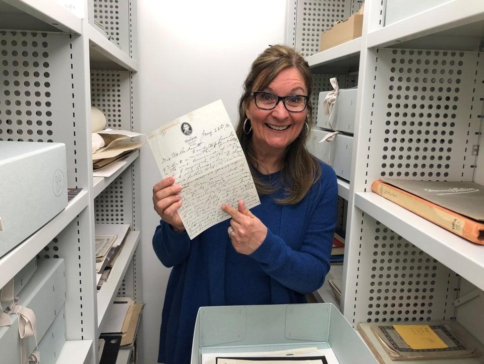 L'archivaria Evelyne Lüthi-Graf cun la brev da John W. Townsend che raschuna da l'emprima glisch electrica.