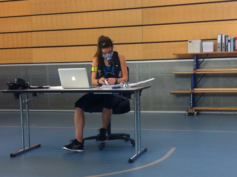 Eine Frau mit Messgerät arbeitet an einem Bürotisch.