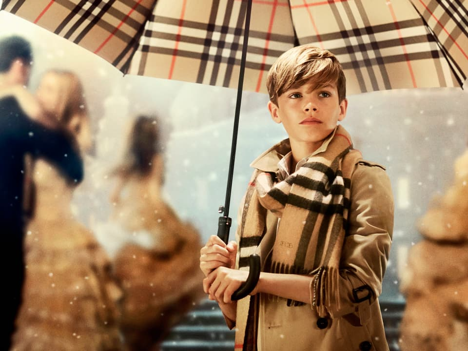 Romeo Beckham unter einem Schirm stehend.