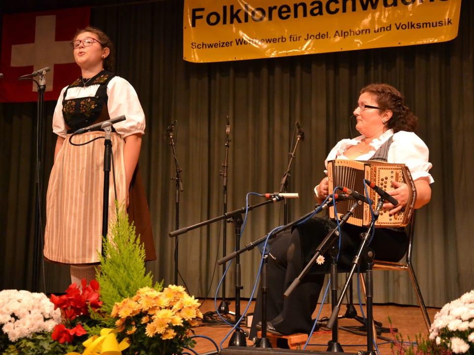 Die junge Jodlerin trägt eine Tracht und steht vor einem Mikrofon. Bei ihrem Auftritt wird sie von einer Musikantin auf dem Schwyzerörgeli begleitet.