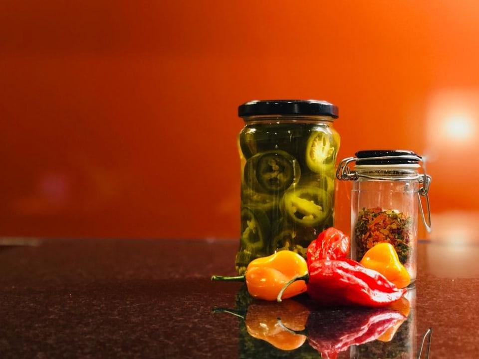 Glas mit Jalapenos und Glas mit Chili-Pulver